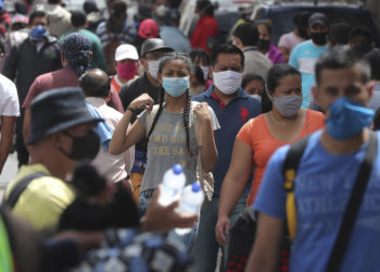 People wearing masks walk in the capital's downtown amid the new coronavirus pandemic in Quito, Ecuador, Monday, June 29, 2020. (AP Photo/Dolores Ochoa)